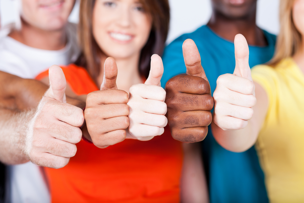 five people hold their thumbs up