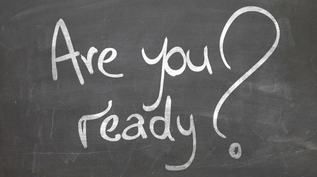"There's a blackboard with ""are you ready?"" written on it in white writing"