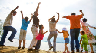 A family throws their hands up in joy on the beach; the photo is taken from the back and with an unfocused lens