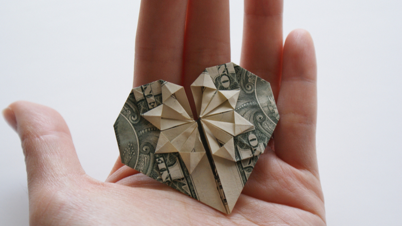A hand holds a dollar bill that is shaped like an origami heart