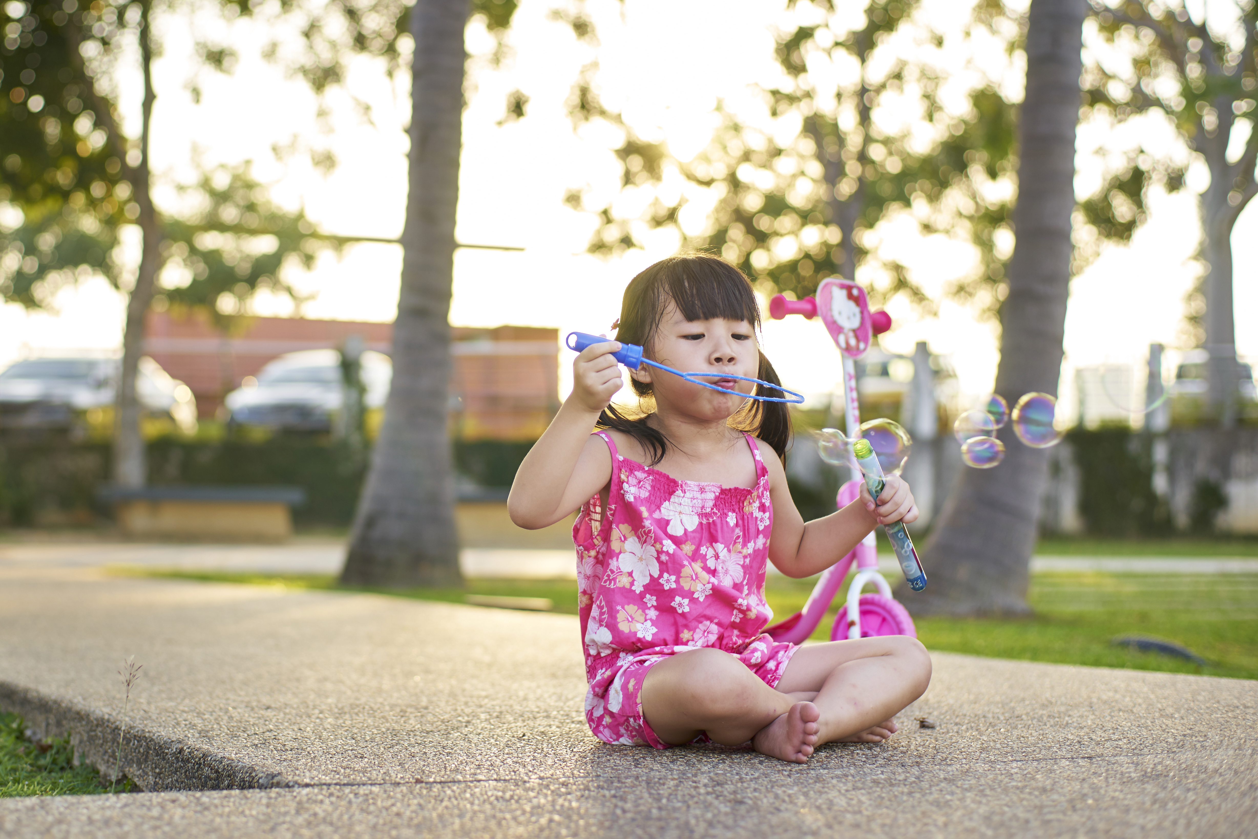 young girl blows bubbles