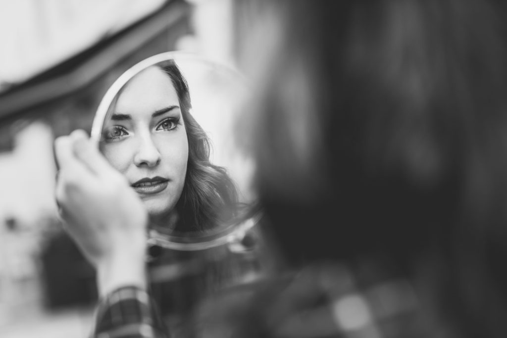 a white woman looks in a mirror; in grayscale