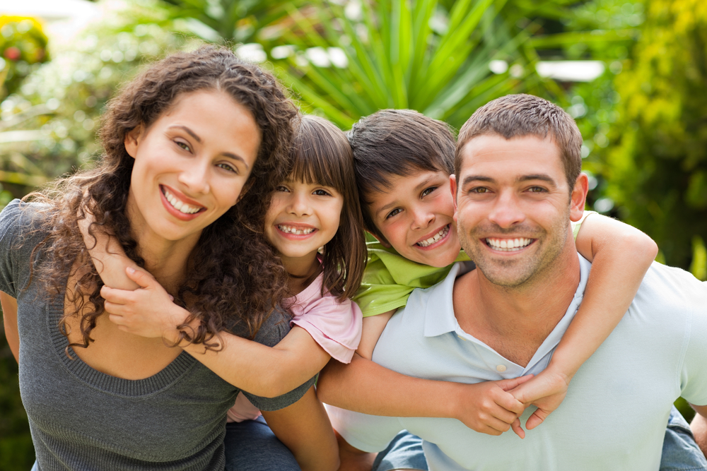 a family of two parents and two kids smiles at the camera