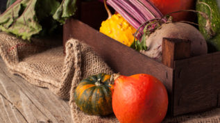 Colorful pumpkins and fresh beet in box on old wooden table with sackcloth