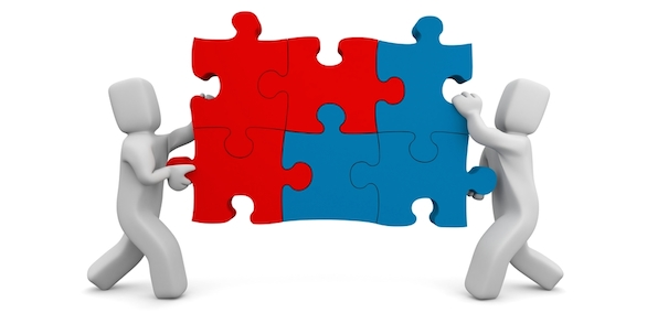 two people push a puzzle piece together