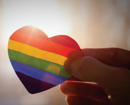 a hand holds up a rainbow printed heart