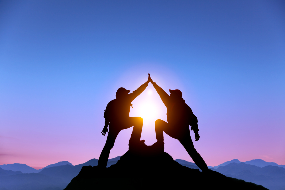 two climbers high five at the top of a mountain
