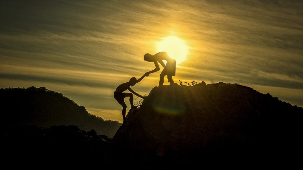 Person helping another person climb a mountain