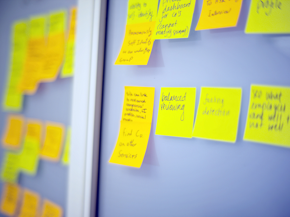 Several bright yellow post its with indistinguishable writing a posted to a grey wall