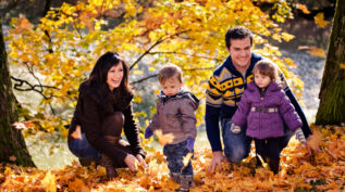 a family with kids plays in a pile of autumn leaves