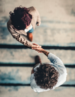 aerial shot of two people shaking hands in a professional work setting