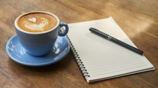 a cup of coffee sits next to a notebook and pen on a wooden table