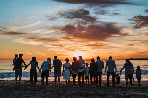 A large group of people standing on the beach, silhouetted by the sunset