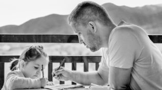 Young girl and father drawing outdoors