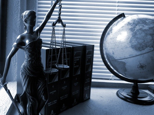 lady justice statue and globe on desk