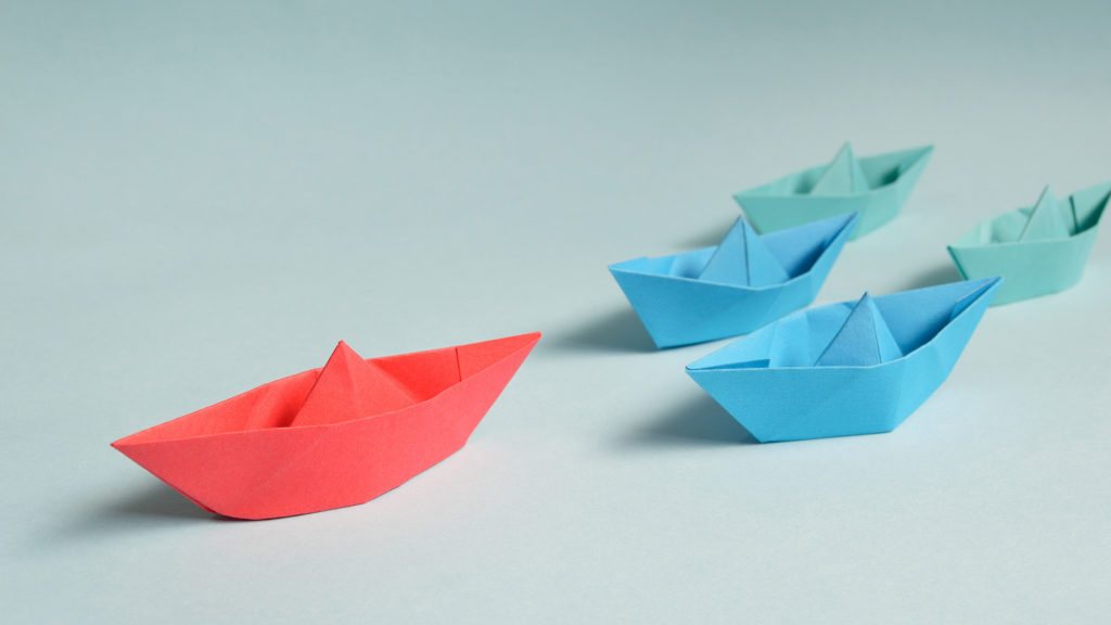 four paper boats with a red boat leading the way