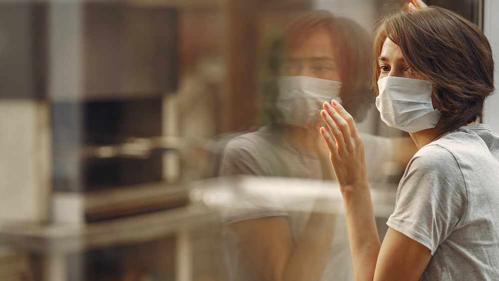 woman wearing mask looking at reflection