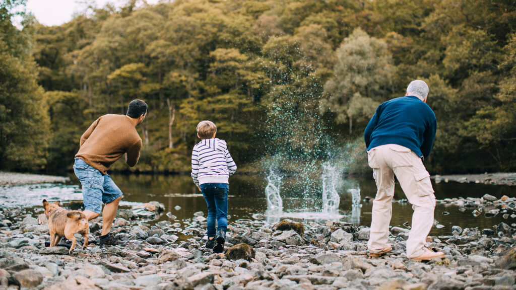 father, son, and grandfather skipping stones - traditions, generations, family cutlure